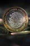 Moeda mexicana no primeiro plano, com fundo escuro Imagem de Stock Royalty Free