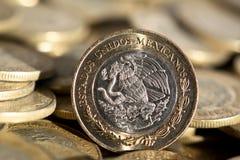 Moeda mexicana no primeiro plano, com muito mais moedas no fundo, macro, horizontal Imagens de Stock