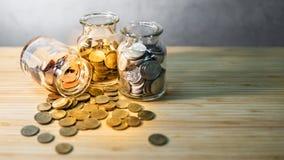 Moeda nos frascos de vidro Dinheiro da economia para a aposentadoria fotografia de stock
