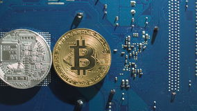Moeda virtual de Bitcoins da prata e do ouro em um fundo da placa de circuito filme
