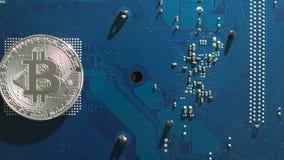 Moeda virtual de prata de Bitcoin em um fundo da placa de circuito filme