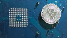 A moeda virtual de prata de Bitcoin gerencie sobre um motoin lento da placa de circuito filme