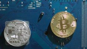 A moeda virtual dourada de Bitcoin gerencie sobre um motoin lento da placa de circuito video estoque