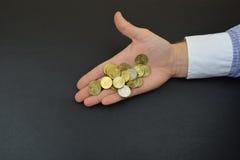 Moedas à disposição Moedas de bronze na mão do ` s do homem Fotografia de Stock Royalty Free