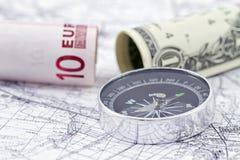 Moedas americanas e europeias com compasso fotos de stock royalty free