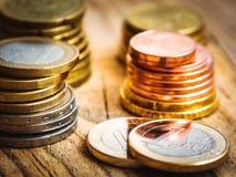 Moedas brancas e douradas brilhantes empilhadas do valor diferente no fundo de madeira, finanças do Euro, investimento, estoque,  Fotos de Stock Royalty Free