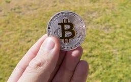 Moedas de Cryptocurrency em uma mão; Bitcoin foto de stock