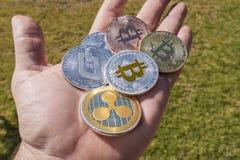 Moedas de Cryptocurrency em uma mão; Bitcoin, ondinha, traço fotografia de stock royalty free