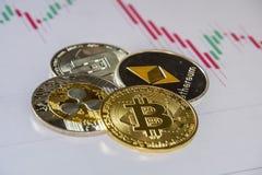 Moedas de Cryptocurrency sobre a troca de velas japonesas gráficas; Bitc imagem de stock