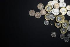 Moedas de libra no fundo preto imagens de stock royalty free
