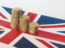 Moedas de libra, Reino Unido sobre a bandeira Imagens de Stock