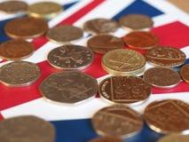 Moedas de libra, Reino Unido sobre a bandeira Fotos de Stock Royalty Free