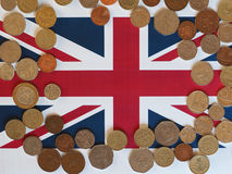Moedas de libra, Reino Unido sobre a bandeira Imagem de Stock Royalty Free
