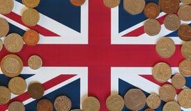 Moedas de libra, Reino Unido sobre a bandeira Fotografia de Stock