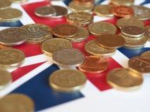 Moedas de libra, Reino Unido sobre a bandeira Fotografia de Stock Royalty Free