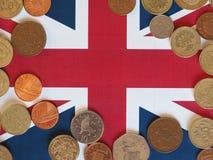 Moedas de libra, Reino Unido sobre a bandeira Foto de Stock Royalty Free