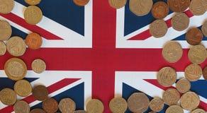 Moedas de libra, Reino Unido sobre a bandeira Imagens de Stock Royalty Free