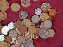 Moedas de libra, Reino Unido sobre o fundo vermelho de veludo Foto de Stock Royalty Free