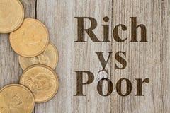 Moedas de ouro com os ricos do texto contra pobres imagens de stock royalty free