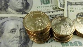 Moedas de ouro da moeda do Estados Unidos e cem notas de dólar video estoque