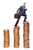 Moedas de ouro de escalada do homem de negócios Fotografia de Stock Royalty Free