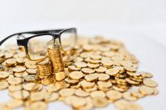Moedas de ouro e glassess Imagem de Stock Royalty Free