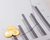 Moedas de ouro em cartas financeiras Foto de Stock Royalty Free