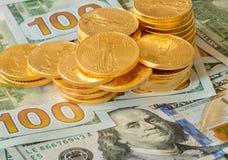 Moedas de ouro empilhadas em notas de dólar novas do projeto 100 Fotografia de Stock