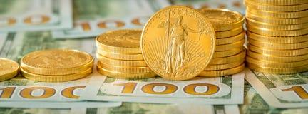 Moedas de ouro empilhadas em notas de dólar novas do projeto 100 Imagem de Stock