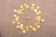 Moedas de ouro falsificadas em torno da forma da seta Imagens de Stock Royalty Free