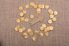 Moedas de ouro falsificadas em torno da forma da seta Foto de Stock