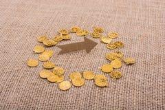 Moedas de ouro falsificadas em torno da forma da seta Imagem de Stock Royalty Free