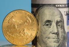 Moedas de ouro puras na frente dos rolos do banco da moeda dos E.U. Imagem de Stock