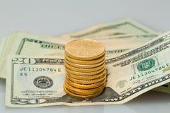 Pilha de $20 notas de dólar com moedas de ouro Fotografia de Stock Royalty Free