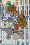 Moedas de países diferentes no fundo do hundre novo Imagens de Stock Royalty Free