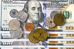 Moedas de países diferentes no fundo do hundre novo Fotografia de Stock Royalty Free