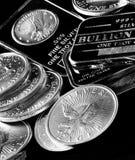 Moedas de prata e barras que representam a riqueza imagem de stock royalty free