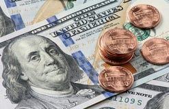 Moedas de um centavo e cédulas do dólar Fotografia de Stock