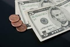 Moedas de um centavo e cinco contas de dólar Imagem de Stock