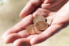 Moedas de um centavo fêmeas A da posse cinco da mão Foto de Stock Royalty Free