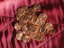 Moedas de um dólar do centavo, Estados Unidos sobre o veludo vermelho Foto de Stock