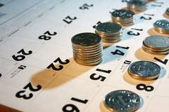 Moedas/dinheiro em um calendário Fotos de Stock Royalty Free