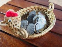 Moedas, dinheiro na cesta, forma feito a mão da galinha, tecida do jacinto de água no fundo de madeira Imagem de Stock