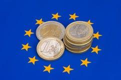 moedas do ââEuro em uma bandeira da UE Fotografia de Stock Royalty Free