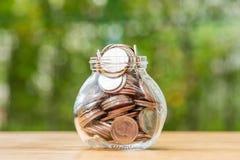 Moedas do baht tailandês que derramam fora do frasco do dinheiro Imagem de Stock Royalty Free
