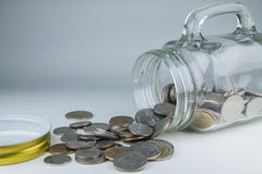 Moedas do baht tailandês que derramam fora do frasco do dinheiro Fotos de Stock