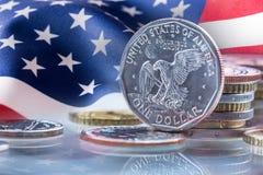 Moedas do dólar e bandeira dos EUA no fundo O dólar dos EUA inventa a posição na borda apoiada em moedas Imagem de Stock Royalty Free