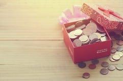 Moedas do dinheiro no presente e na caixa de presente Fotografia de Stock Royalty Free