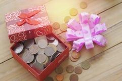 Moedas do dinheiro no presente e na caixa de presente Foto de Stock
