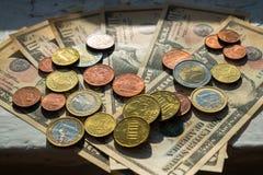 Moedas do Euro de denominações diferentes no fundo das notas de dólar Close-up de diversas euro- moedas Conceito da troca no fotografia de stock